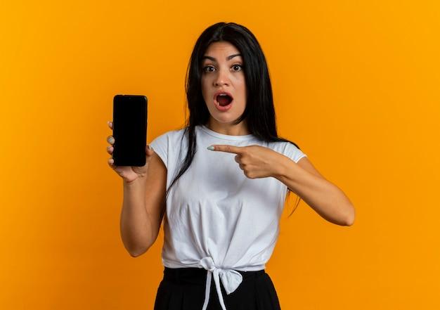 Geschokt jong kaukasisch meisje houdt en wijst op de telefoon