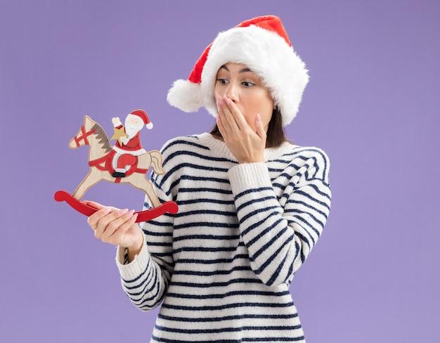 Geschokt jong kaukasisch meisje met kerstmuts zet hand op mond houden en kijken naar santa op schommelpaard decoratie geïsoleerd op paarse muur met kopie ruimte