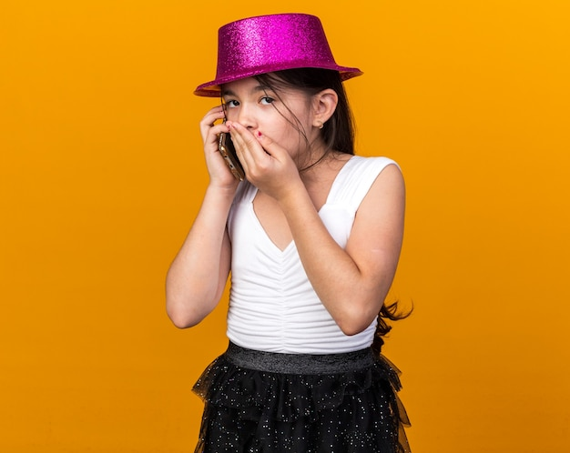 Geschokt jong kaukasisch meisje met paarse feestmuts hand op mond zetten praten over telefoon geïsoleerd op oranje muur met kopie ruimte