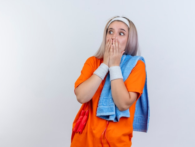 Geschokt jong kaukasisch sportief meisje met beugels en met touwtjespringen om nek hoofdband polsbandjes dragen handdoek op schouder legt handen op mond kijken kant op witte muur