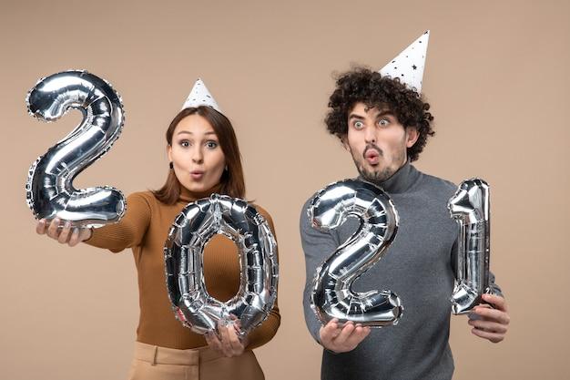 Geschokt jong koppel dragen nieuwe jaar hoed vormt voor camera meisje en en jongen met en op grijs tonen