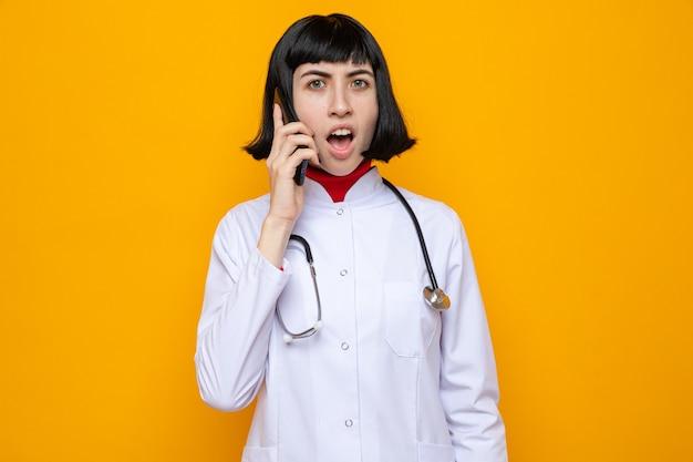 Geschokt jong mooi kaukasisch meisje in doktersuniform met stethoscoop die aan de telefoon praat