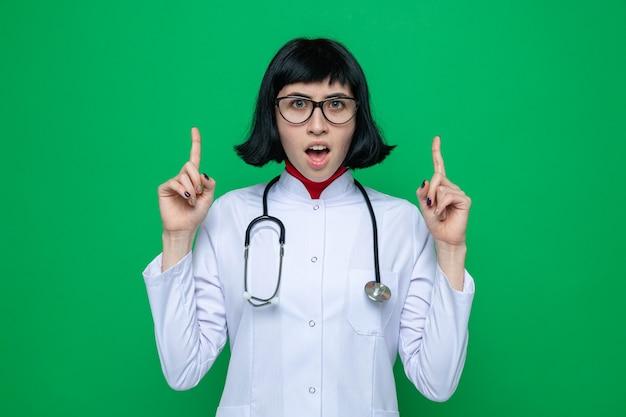Geschokt jong mooi met een bril, een blanke vrouw in doktersuniform met een stethoscoop die omhoog wijst met de handen