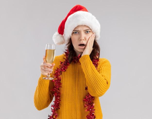 Geschokt jong slavisch meisje met kerstmuts en met slinger om nek legt hand op gezicht en houdt glas champagne geïsoleerd op een witte muur met kopieerruimte