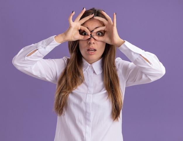 Geschokt jong, vrij blank meisje kijkt naar camera door vingers geïsoleerd op paarse muur met kopieerruimte