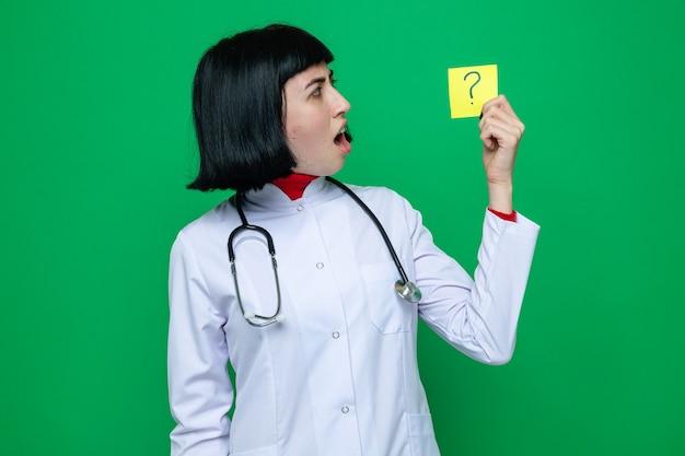Geschokt jong, vrij kaukasisch meisje in doktersuniform met een stethoscoop die de vraag vasthoudt en bekijkt