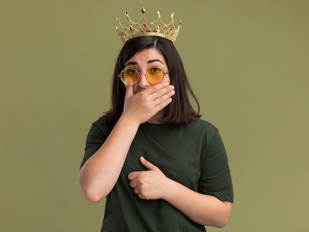 Geschokt jong vrij kaukasisch meisje in zonnebril met kroon legt hand op mond