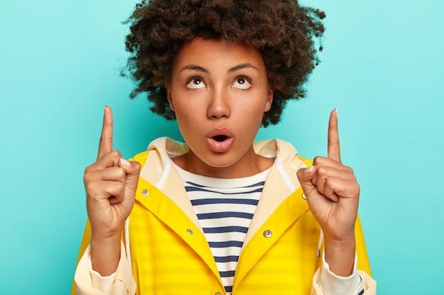 Geschokt jong vrouwtje met afro-kapsel wijst naar boven, opent mond, naar boven gericht met verrassing, gekleed in gestreepte trui en gele regenjas, geïsoleerd op blauwe achtergrond.