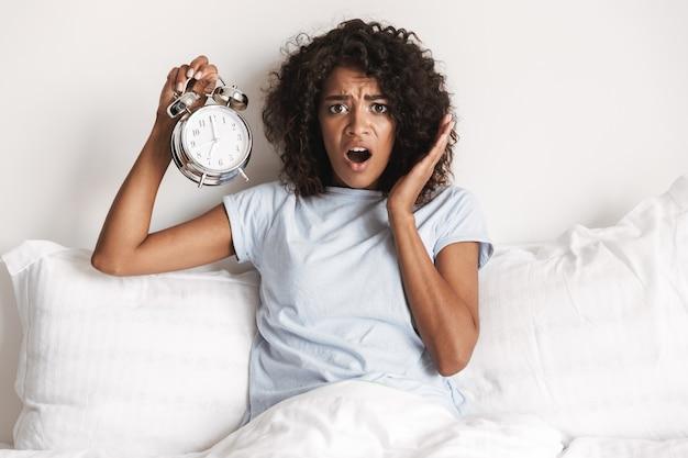 Geschokt jonge afrikaanse vrouw die wekker toont