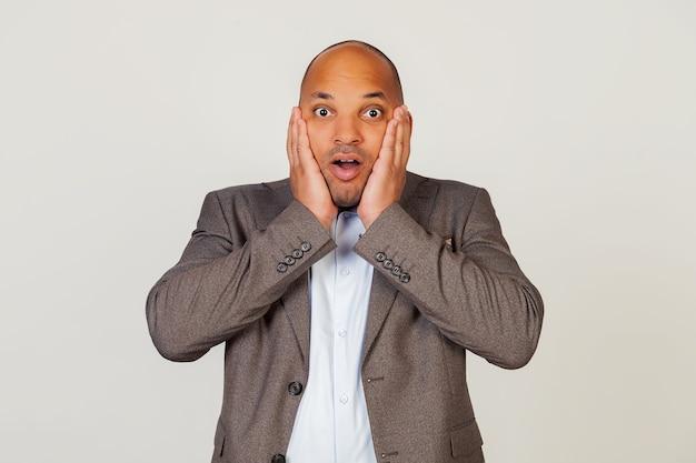 Geschokt jonge afro-amerikaanse man zakenman uiting van verbazing en verbazing, zijn gezicht aan te raken en zijn lippen vouwen, staat in een verdoving en bril naar de camera, onder de indruk.