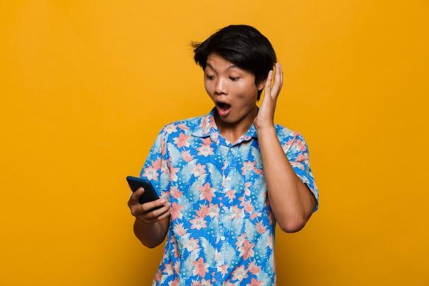 Geschokt jonge aziatische man permanent geïsoleerd over gele ruimte met behulp van mobiele telefoon.