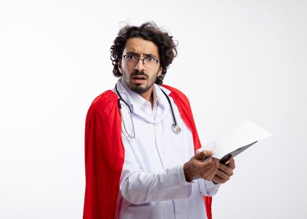 Geschokt jonge blanke superheld man in optische bril met doktersuniform met rode mantel en met stethoscoop om nek houdt klembord vast