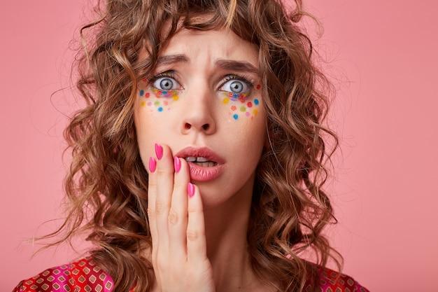 Geschokt jonge blauwogige brunette vrouw met feestelijk kapsel houdt haar wang met palm vast en kijkt met grote ogen geopend, poseren in gekleurde top met patroon