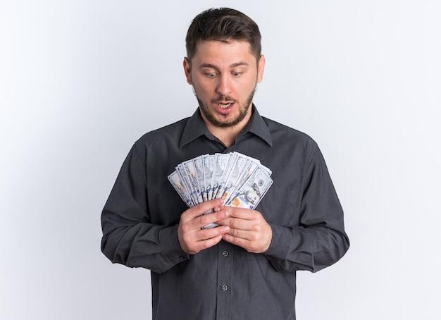 Geschokt jonge blonde knappe man met geld naar beneden te kijken