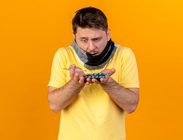 Geschokt jonge blonde zieke slavische man die betrekking heeft op mond met sjaal houdt en kijkt naar verpakkingen van medische pillen en spuit geïsoleerd op oranje muur met kopie ruimte