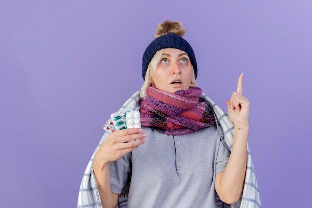 Geschokt jonge blonde zieke slavische vrouw die de winterhoed draagt