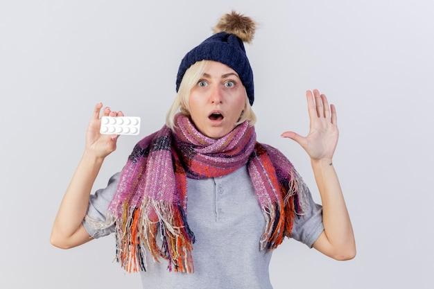 Geschokt jonge blonde zieke slavische vrouw met muts en sjaal