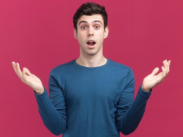 Geschokt jonge brunette blanke man hand in hand open geïsoleerd op roze muur met kopie ruimte