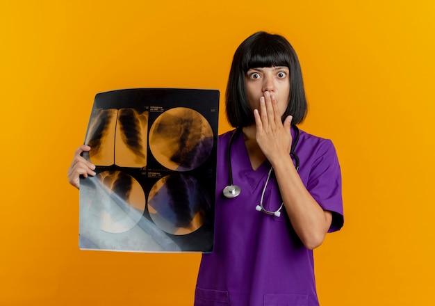 Geschokt jonge brunette vrouwelijke arts in uniform met stethoscoop legt hand op mond met x-ray resultaat