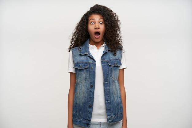 Geschokt jonge donkerhuidige brunette krullende vrouw kijkt verbaasd met grote ogen en mond geopend, handen langs het lichaam houden terwijl poseren op wit