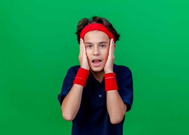Geschokt jonge knappe sportieve jongen met hoofdband en polsbandjes met beugels handen houden op het hoofd geïsoleerd op groene muur met kopie ruimte