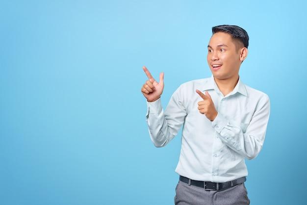Geschokt jonge knappe zakenman wijzende vinger weg naar kopieerruimte op blauwe achtergrond