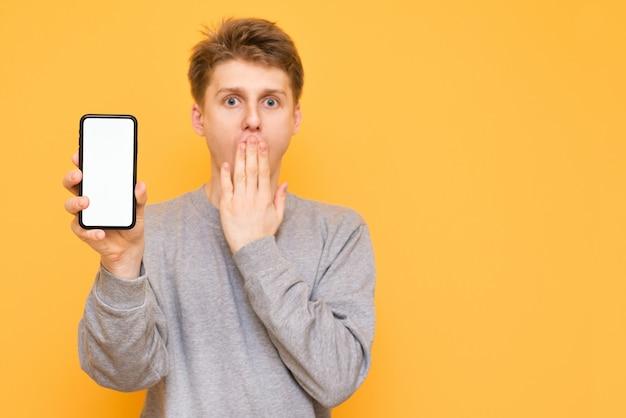 Geschokt jonge man in casual kleding houdt in zijn hand een moderne smartphone met een wit scherm en kijkt verbaasd over de camera op geel