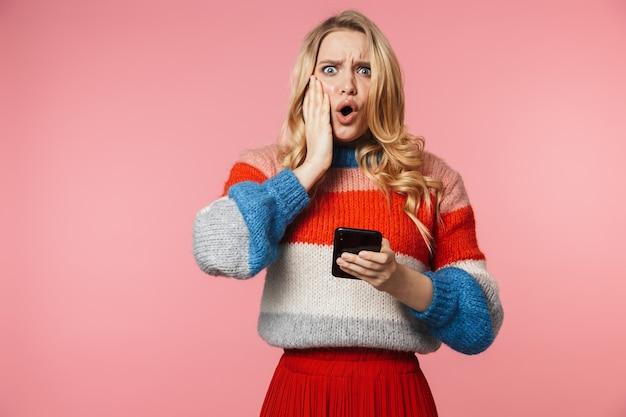 Geschokt jonge mooie mooie vrouw poseren geïsoleerd over roze muur met behulp van mobiele telefoon