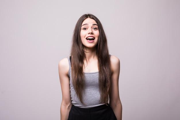 Geschokt jonge vrouw die met open mond kijkt. geïsoleerd op grijs