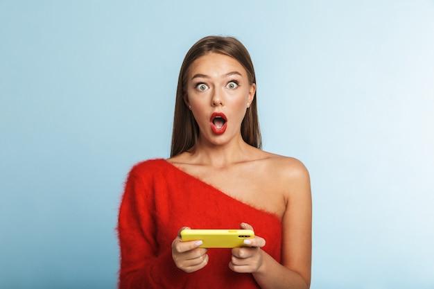 Geschokt jonge vrouw geïsoleerd poseren, spelletjes spelen via de mobiele telefoon.