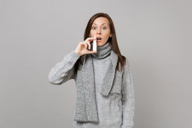 Geschokt jonge vrouw in grijze trui, sjaal houden met behulp van neusdruppels geïsoleerd op grijze muur achtergrond in studio. gezonde levensstijl, behandeling van zieke ziektes, concept van het koude seizoen. bespotten kopie ruimte.