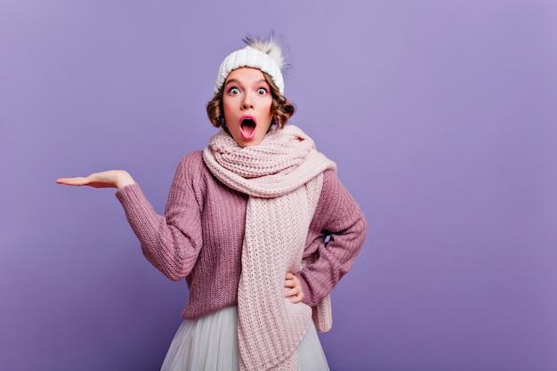 Geschokt jonge vrouw in lange gebreide sjaal staande op paarse muur met open mond. meisje in trendy winteraccessoires die verrast emoties uitdrukken.
