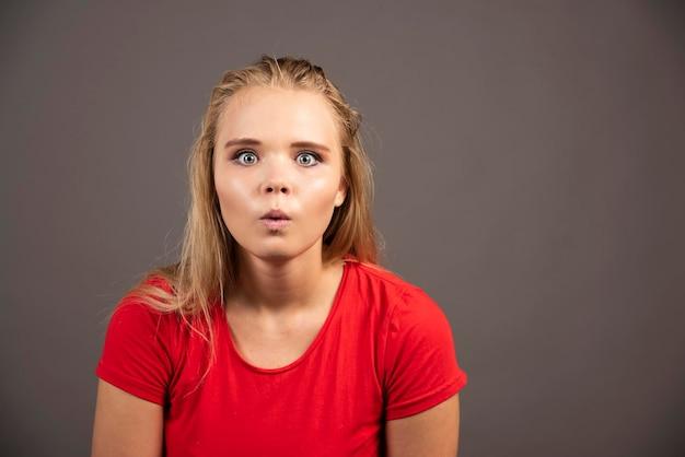Geschokt jonge vrouw in rood shirt op donkere achtergrond. hoge kwaliteit foto