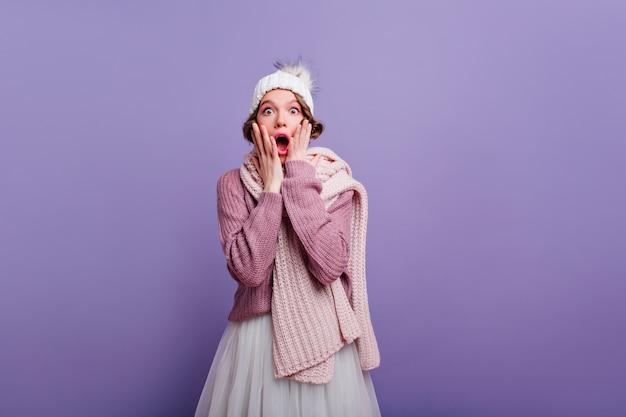 Geschokt jonge vrouw in trendy hoed gillen op paarse muur. indoor foto van stijlvol meisje in sjaal en trui gezicht aan te raken en verbazing te uiten.