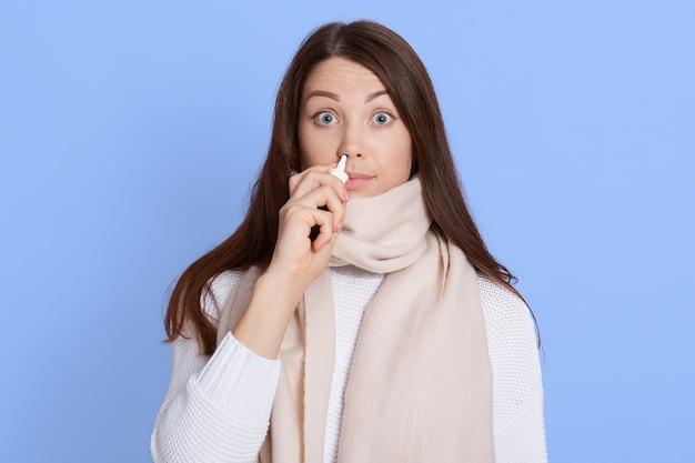 Geschokt jonge vrouw in witte trui en sjaal houden en gebruiken neusdruppels met grote ogen geïsoleerd op blauwe muur muur, donkerharige dame voelt zich slecht, lijdt aan loopneus, verkouden.