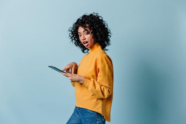 Geschokt jonge vrouw met behulp van digitale tablet