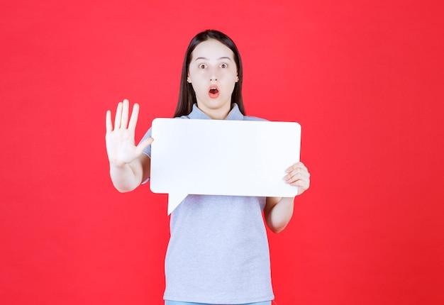 Geschokt jonge vrouw met bord en gebaren stop