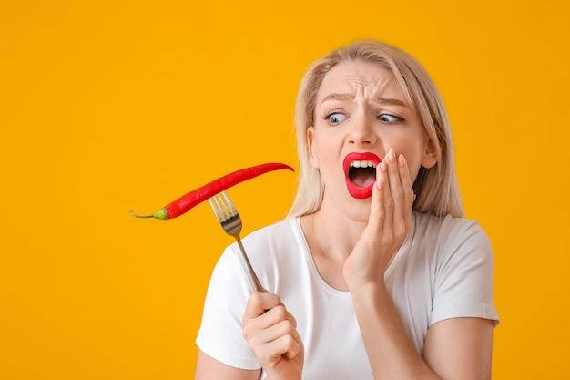 Geschokt jonge vrouw met chili peper op kleur oppervlak
