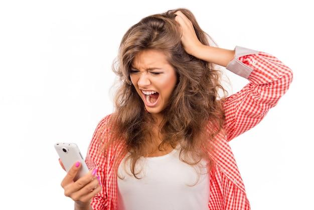 Geschokt jonge vrouw met telefoon en schreeuwen