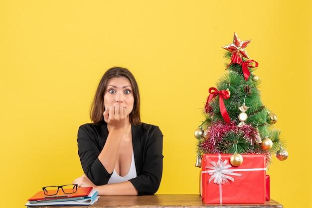 Geschokt jonge vrouw op zoek naar iets met verbaasde gezichtsuitdrukking zittend aan een tafel in de buurt van versierde kerstboom op kantoor op geel