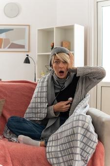 Geschokt jonge zieke slavische vrouw met sjaal om haar nek gewikkeld in plaid met wintermuts hand op het hoofd zetten en haar pulsen meten met een stethoscoop zittend op de bank in de woonkamer
