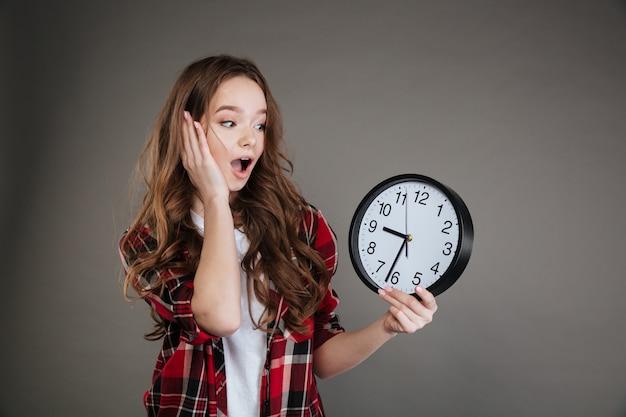 Geschokt jongedame bedrijf klok. opzij kijken.