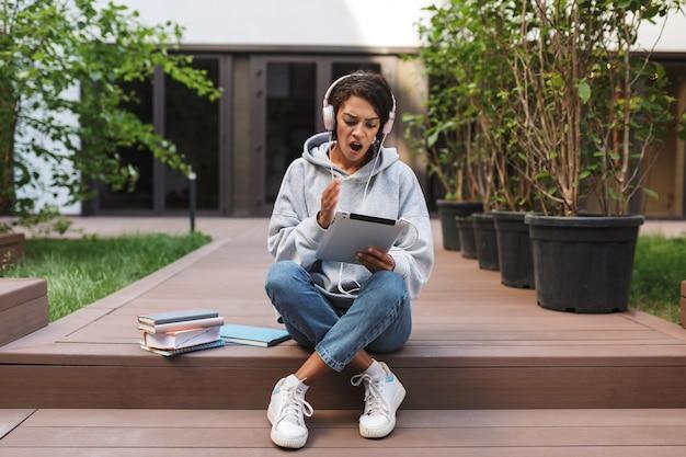 Geschokt jongedame in koptelefoon zitten en verbaasd