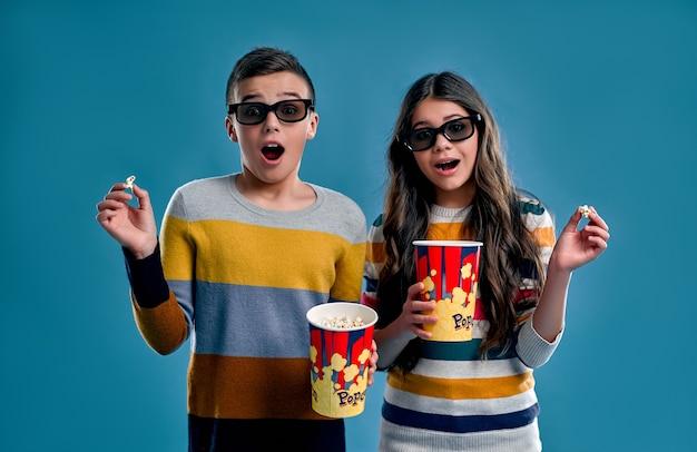 Geschokt jongen en meisje eten popcorn in 3d-bril kijken naar een enge film geïsoleerd op een blauw.