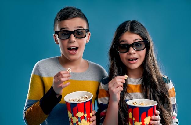 Geschokt jongen en meisje eten popcorn in 3d-bril kijken naar een film geïsoleerd op een blauw.