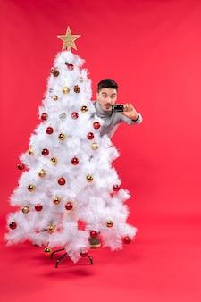 Geschokt jongvolwassene in een grijze blouse die achter de versierde kerstboom staat en zijn telefoon op rood bekijkt