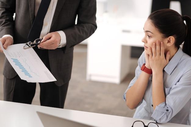 Geschokt kantoormedewerker die de ogen wijd open houdt terwijl hij in een halve positie zit de wangen aan te raken