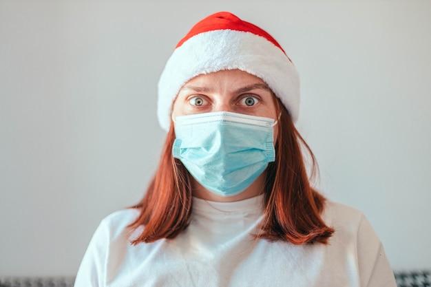 Geschokt kaukasisch meisje in kerstmuts en een beschermend medisch masker onderzoekt de camet