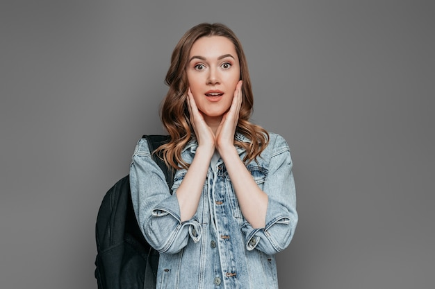 Geschokt kaukasisch studentenmeisje dat haar gezicht met twee handen houdt en de camera bekijkt die op donkergrijze muur wordt geïsoleerd. examens concept