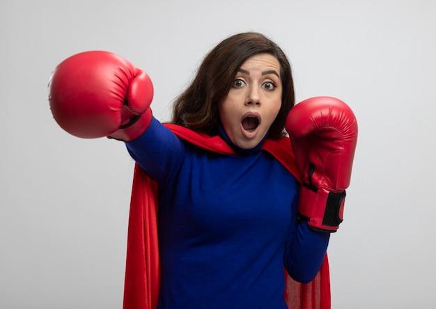Geschokt kaukasisch superheldmeisje met rode cape die het dragen van bokshandschoenen beweert te slaan